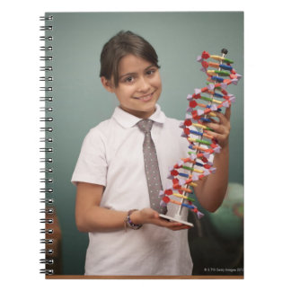 Young schoolgirl holds a colorful model spiral notebook
