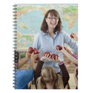 young students presenting apples to teacher notebook