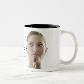 Young woman calculating equations on glass Two-Tone coffee mug