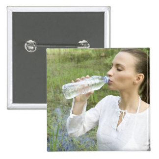 young woman drinking water from bottle 15 cm square badge