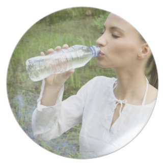 young woman drinking water from bottle dinner plates