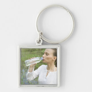 young woman drinking water from bottle key ring