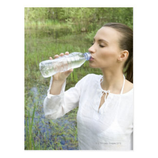 young woman drinking water from bottle postcard