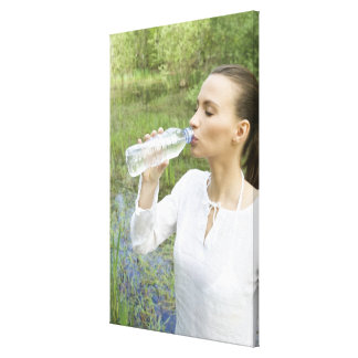 young woman drinking water from bottle stretched canvas print