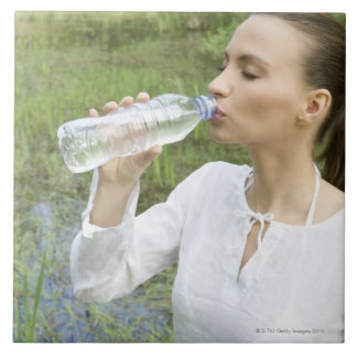 young woman drinking water from bottle tiles
