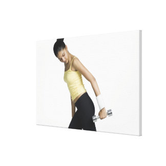 Young woman exercising with a dumbbell canvas print