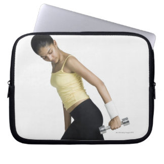 Young woman exercising with a dumbbell laptop sleeve
