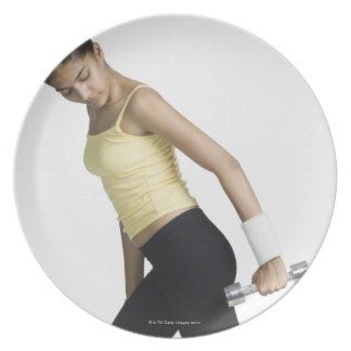 Young woman exercising with a dumbbell plate