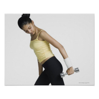 Young woman exercising with a dumbbell poster