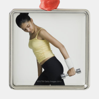 Young woman exercising with a dumbbell Silver-Colored square decoration