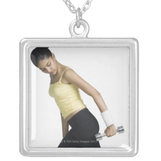 Young woman exercising with a dumbbell silver plated necklace
