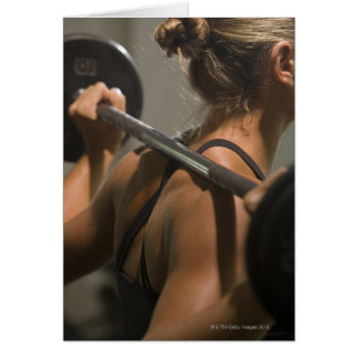 Young woman exercising with barbell, rear view greeting card