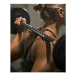 Young woman exercising with barbell, rear view poster