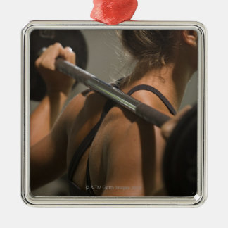 Young woman exercising with barbell, rear view Silver-Colored square decoration