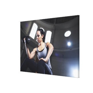 Young woman exercising with dumbbell canvas print