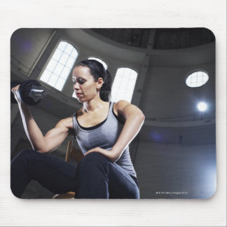 Young woman exercising with dumbbell mouse mat