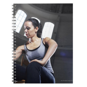 Young woman exercising with dumbbell notebook