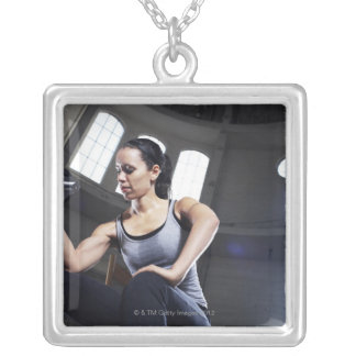 Young woman exercising with dumbbell silver plated necklace