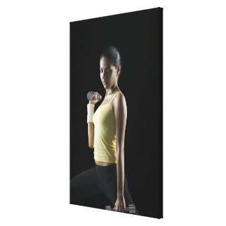 Young woman exercising with dumbbells canvas print