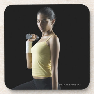 Young woman exercising with dumbbells coaster