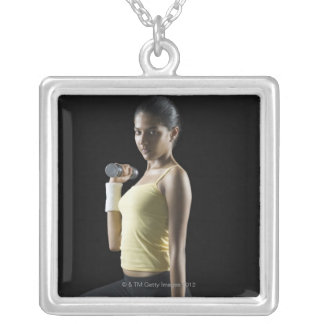 Young woman exercising with dumbbells silver plated necklace