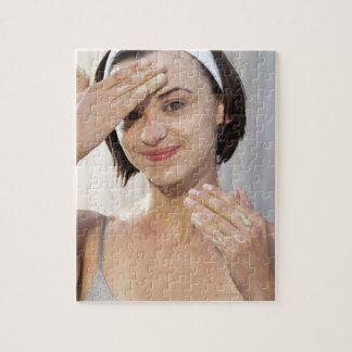 Young woman exfoliating face, smiling, portrait, jigsaw puzzle