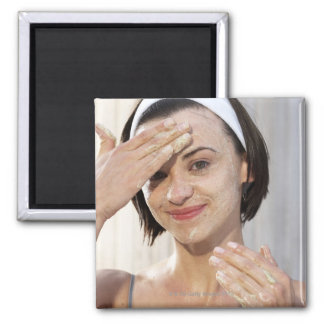 Young woman exfoliating face, smiling, portrait, magnet