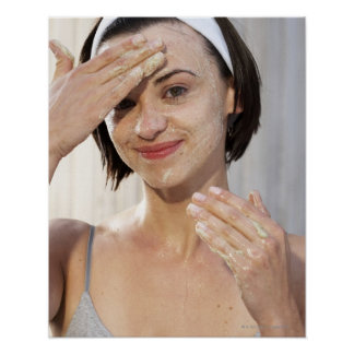 Young woman exfoliating face, smiling, portrait, poster