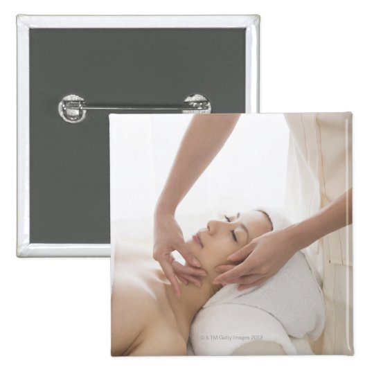 Young woman having facial massage 15 cm square badge
