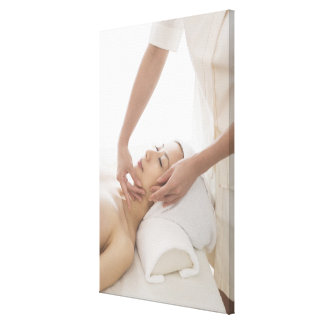Young woman having facial massage canvas print