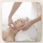 Young woman having facial massage coaster