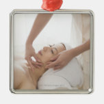 Young woman having facial massage christmas tree ornament