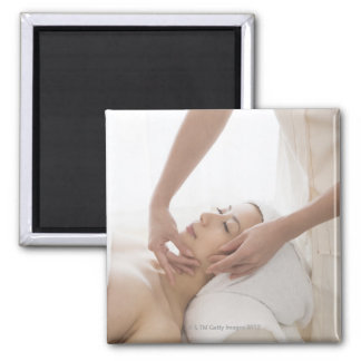 Young woman having facial massage fridge magnet