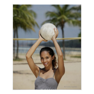 Young woman holding volleyball and smiling at poster