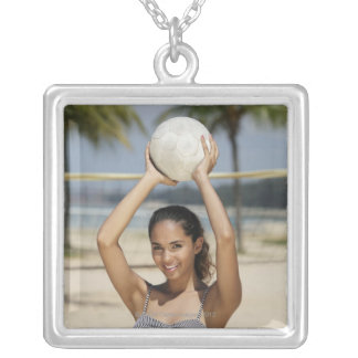 Young woman holding volleyball and smiling at silver plated necklace