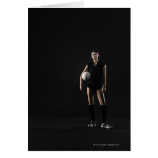 Young woman holding volleyball, portrait card