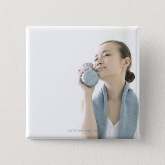 young woman holding water bottle to face 15 cm square badge