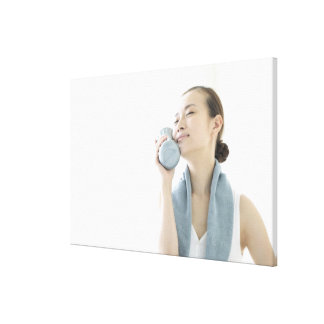 young woman holding water bottle to face canvas print
