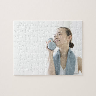 young woman holding water bottle to face jigsaw puzzle