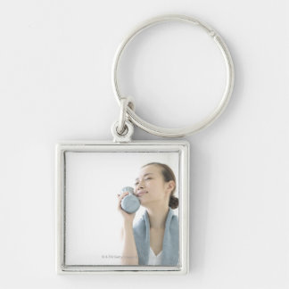 young woman holding water bottle to face Silver-Colored square key ring