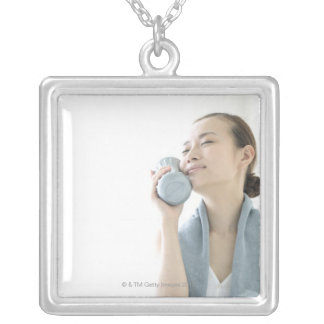 young woman holding water bottle to face silver plated necklace