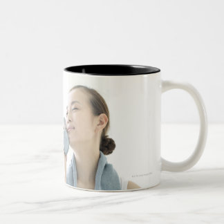 young woman holding water bottle to face Two-Tone coffee mug