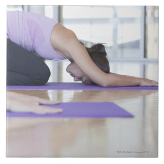 young woman in the downward dog position during large square tile
