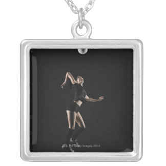 Young woman jumping to hit volleyball, side view silver plated necklace
