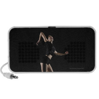 Young woman jumping to hit volleyball, side view mp3 speakers