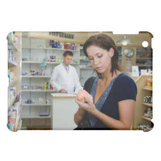 Young woman looking at medicine in pharmacy, iPad mini covers