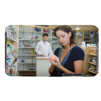 Young woman looking at medicine in pharmacy, iPod touch covers