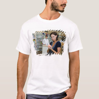 Young woman looking at medicine in pharmacy, T-Shirt