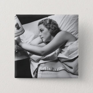 Young woman lying on bed turning off lamp on 15 cm square badge