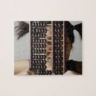 Young woman peering through abacus. jigsaw puzzle
